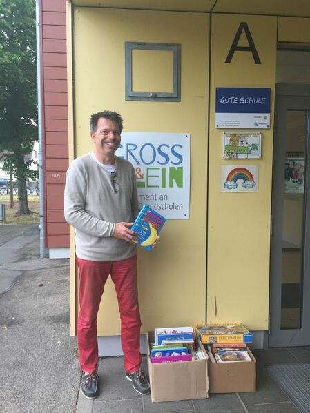 Stephan Eickschen vor der Laurentiusschule beim Verteilen von Büchern